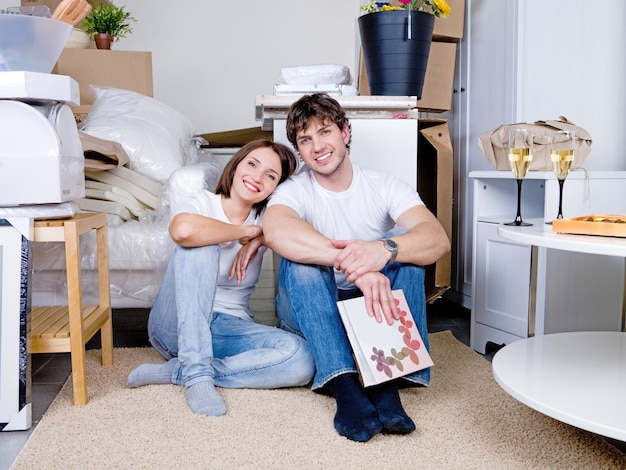 Jong gelukkig lachend paar zittend op de vlotter in de flat na het verplaatsen