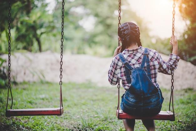 Jong gelukkig meisje die op een schommeling in het park berijden