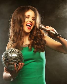 Jong gelukkig meisje zingen in microfoon op feestje