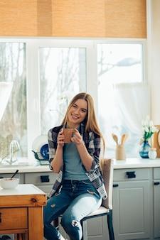 Jong gelukkig meisje zit in de keuken met een mok in haar handen en glimlacht