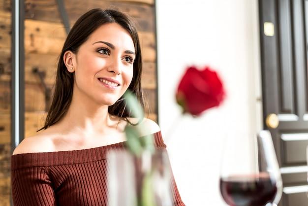 Jong gelukkig paar dat de dag van valentine met een diner viert dat thuis wijn, toejuicht drinkt.