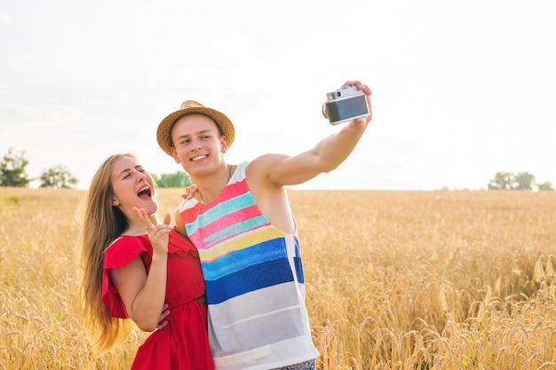 Jong gelukkig paar dat een selfie in het veld neemt