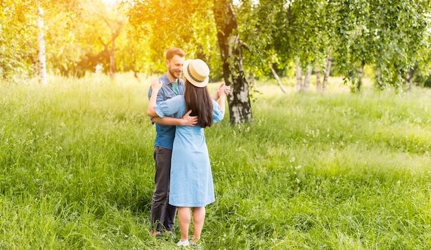 Jong gelukkig paar dat in zonnige dag in aard danst