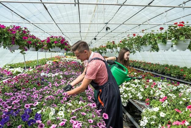 Jong gelukkig paar dat met bloemen bij industriële serre werkt. levensstijl