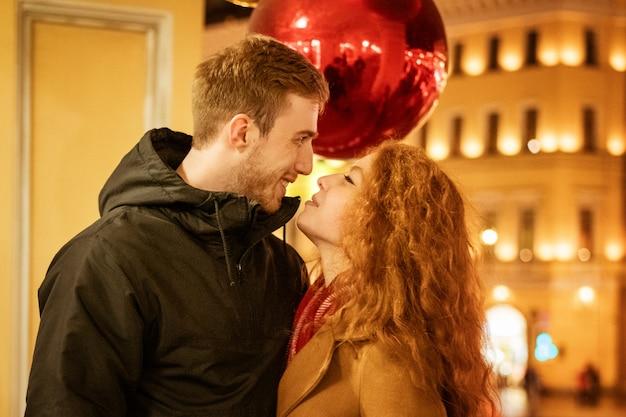 Jong gelukkig paar dat 's avonds door de stad loopt
