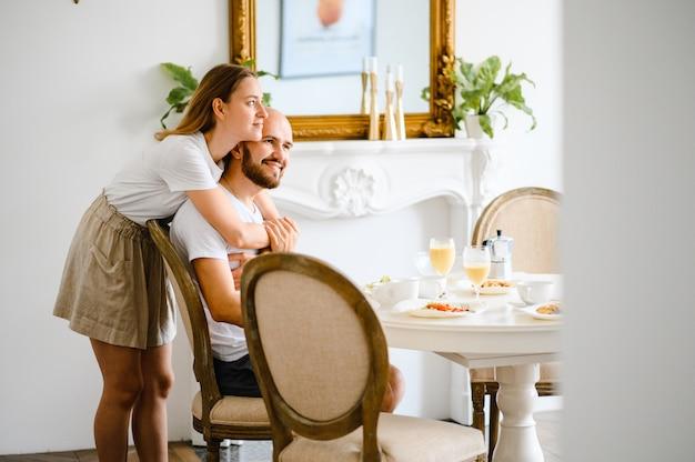 Jong gelukkig paar dat samen ontbijt heeft thuis.