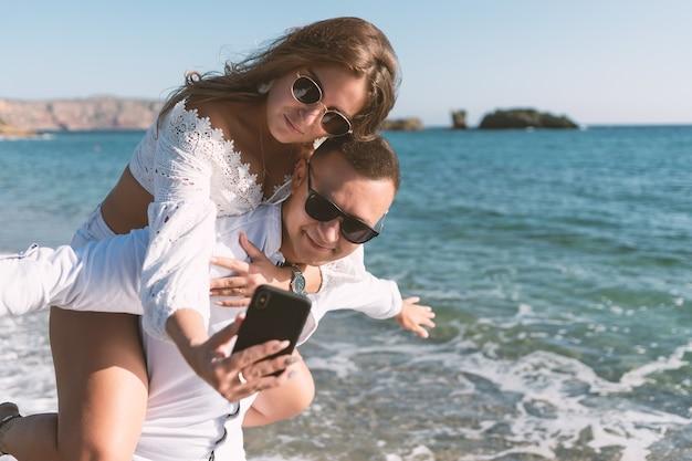 Jong gelukkig paar dat selfie op het strand neemt.
