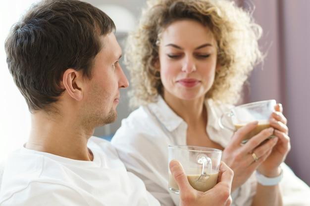 Jong gelukkig paar dat thuis koffie drinkt