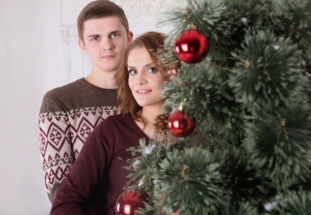 Jong gelukkig paar die dichtbij de kerstboom omhelzen die nieuw jaar vieren die samen glimlachen