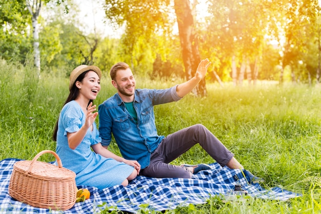 Jong gelukkig paar die en op picknick in aard golven glimlachen