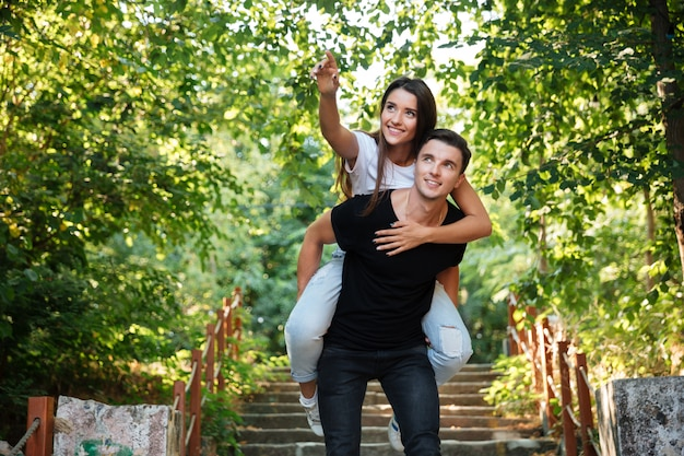 Jong gelukkig paar die op de rug van rit genieten bij het park