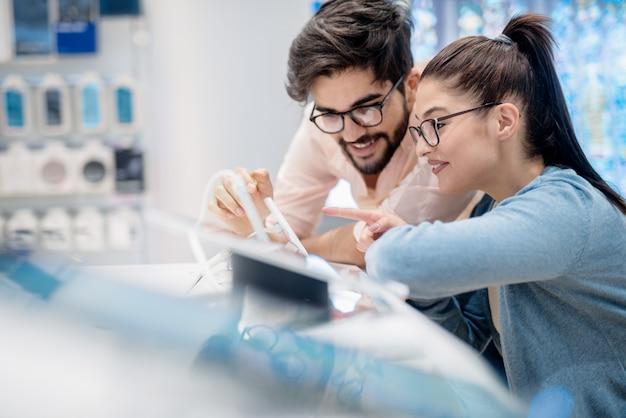 Jong gelukkig paar die specificaties voor tablet kijken die zij willen kopen terwijl het leunen op nieuwe technologieënconcept.