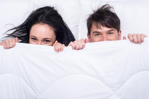 Jong gelukkig paar in een bed