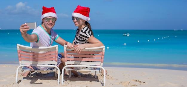 Jong gelukkig paar in rode kerstmanhoeden die een foto op celtelefoon nemen