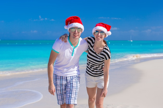 Jong gelukkig paar in rode kerstmanhoeden op tropisch strand