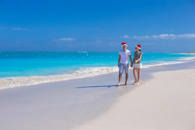 Jong gelukkig paar in rode kerstmanhoeden op tropisch zandstrand