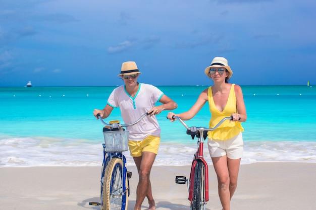 Jong gelukkig paar met fietsen op wit zandstrand