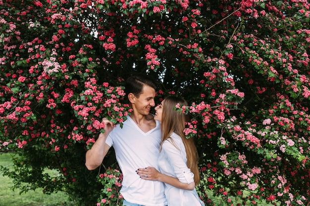 Jong gelukkig paar verliefd buitenshuis. liefdevolle man en vrouw op een wandeling in een bloeiende lente park