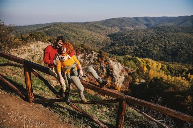 Jong gelukkig paar verliefd vrije tijd doorbrengen in de natuur. paar zittend op een houten hek en knuffelen. het is een mooie zonnige herfstdag.