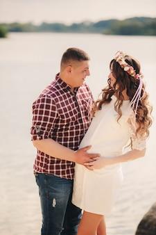 Jong gelukkig romantisch zwanger paar die op aard dichtbij meer in de zomerpark koesteren. zwangere vrouw die een baby verwacht. toekomstige vader en moeder, familie. moederdag, vaderdag