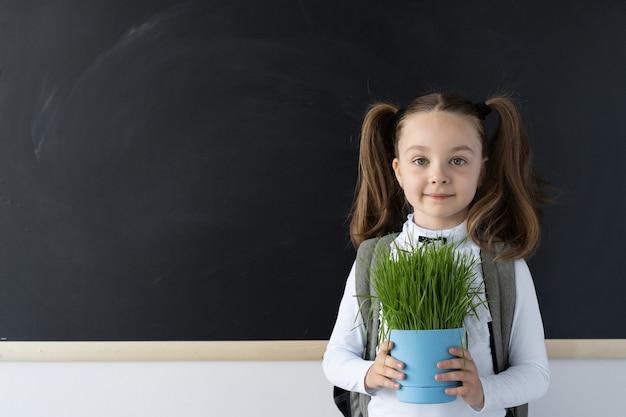 Jong gelukkig schoolmeisje staat op het bord