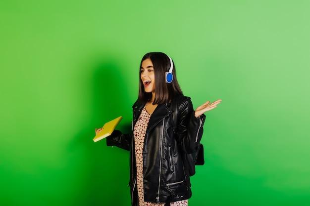Jong gelukkig studentenmeisje in zwart leerjasje met rugzak en geel notitieboekje, dat op groen oppervlak wordt geïsoleerd. ze luisterde naar muziek met een koptelefoon.
