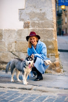 Jong gelukkig toeristenmeisje met gelukkige glimlach in een blauwe laag en een bourgondische hoed met jong hondenras schor in de straat