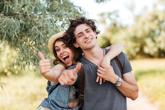 Jong gelukkig vrolijk paar duimen opdagen en knuffelen op bos achtergrond