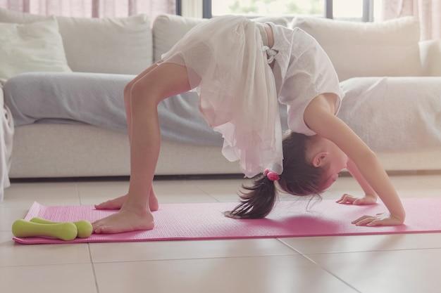 Jong gemengd aziatisch meisje training training thuis, doen lichaamsgewicht vloer oefeningen, kijken naar online streaming video's op laptop, sociale afstands concept