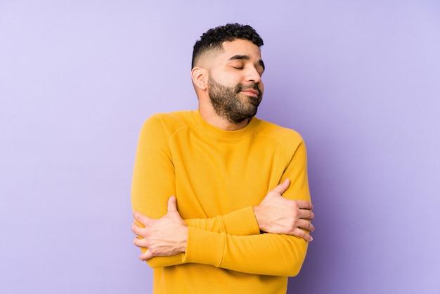 Jong gemengd ras arabische man geïsoleerde knuffels, zorgeloos en gelukkig glimlachen.