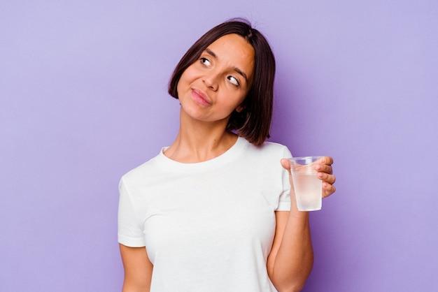 Jong gemengd ras dat een glas water houdt dat op purpere achtergrond wordt geïsoleerd die droomt van het bereiken van doelstellingen en doeleinden