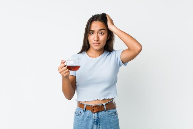 Jong gemengd ras indiër die een theekop houdt die wordt geschokt, heeft zij belangrijke vergadering herinnerd.