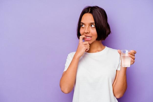 Jong gemengd ras met een glas water geïsoleerd op paarse achtergrond ontspannen denken aan iets kijken naar een kopie ruimte.