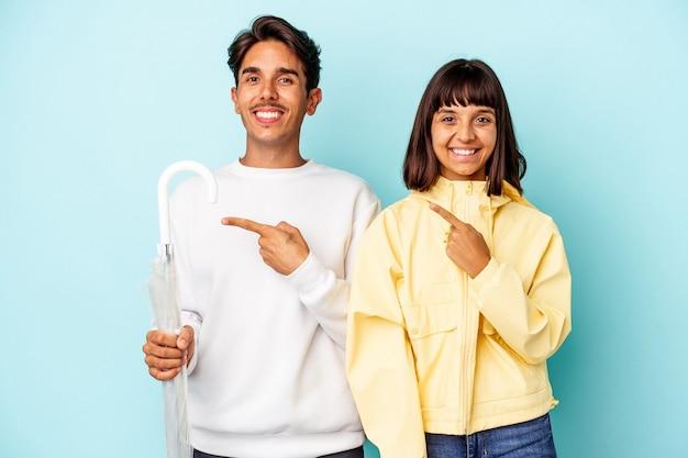 Jong gemengd ras paar bedrijf paraplu geïsoleerd op blauwe achtergrond glimlachend en opzij wijzend, iets tonen op lege ruimte.