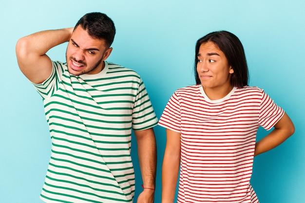 Jong gemengd ras paar geïsoleerd op blauwe achtergrond achterhoofd aanraken, denken en een keuze maken.