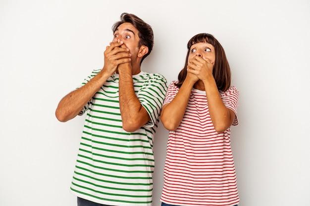 Jong gemengd ras paar geïsoleerd op een witte achtergrond doordachte op zoek naar een kopie ruimte die mond met de hand bedekt.