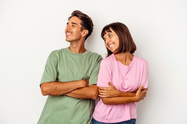 Jong gemengd ras paar geïsoleerd op een witte achtergrond glimlachend vertrouwen met gekruiste armen.