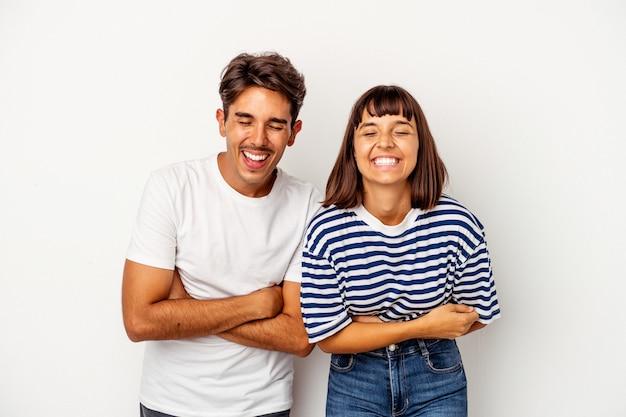 Jong gemengd ras paar geïsoleerd op een witte achtergrond lachen en plezier maken.