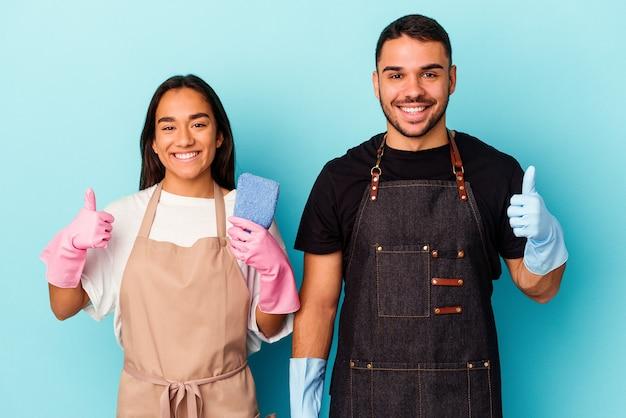 Jong gemengd ras paar schoonmaken huis geïsoleerd op blauwe achtergrond glimlachend en duim omhoog