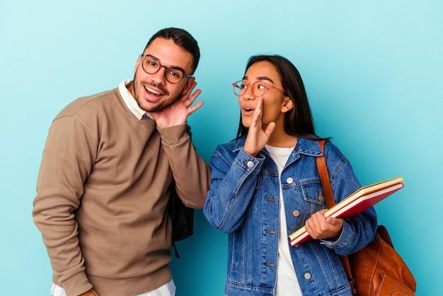 Jong gemengd ras studentenpaar geïsoleerd op blauw zegt een geheim heet remnieuws en kijkt opzij