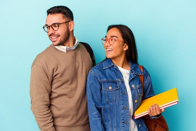 Jong gemengd ras studentenpaar geïsoleerd op blauwe achtergrond kijkt opzij glimlachend, vrolijk en aangenaam.