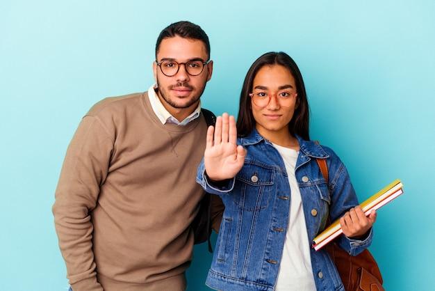 Jong gemengd ras studentenpaar geïsoleerd op een blauwe achtergrond, staande met uitgestrekte hand met stopbord, waardoor je wordt voorkomen.