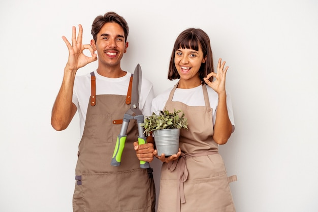 Jong gemengd ras tuinman paar geïsoleerd op een witte achtergrond vrolijk en zelfverzekerd weergegeven: ok gebaar.