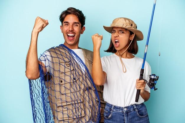Jong gemengd ras visserspaar geïsoleerd op blauwe achtergrond die vuist opheft na een overwinning, winnaar concept.