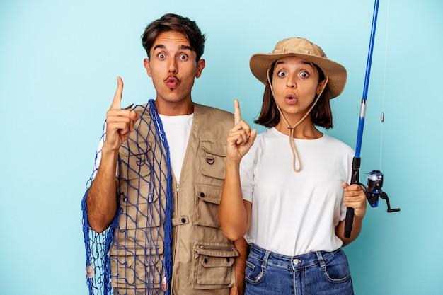 Jong gemengd ras visserspaar geïsoleerd op blauwe achtergrond met een geweldig idee, concept van creativiteit.