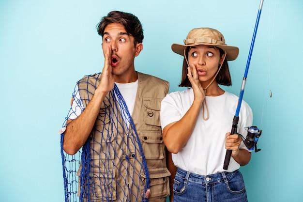 Jong gemengd ras visserspaar geïsoleerd op blauwe achtergrond zegt een geheim heet remnieuws en kijkt opzij