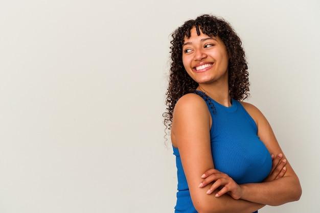 Jong gemengd ras vrouw geïsoleerd op een witte achtergrond glimlachend vertrouwen met gekruiste armen.