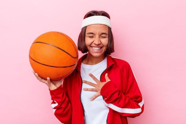 Jong gemengd ras vrouw speelbasketbal geïsoleerd op roze muur lacht hardop hand op de borst te houden.