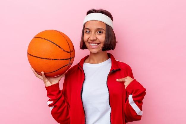 Jong gemengd ras vrouw speelbasketbal geïsoleerd op roze muur persoon met de hand wijzend naar een shirt kopie ruimte, trots en zelfverzekerd