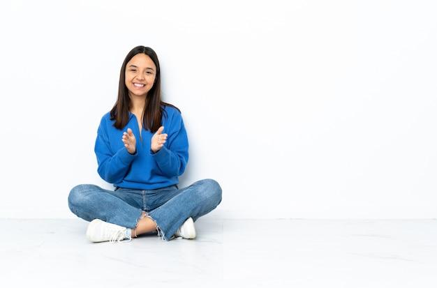 Jong gemengd ras vrouw zittend op de vloer geïsoleerd op witte muur applaudisseren na presentatie in een conferentie